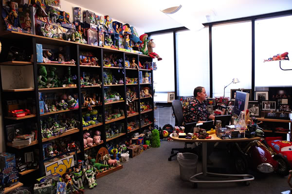 """CARS 2"" BEHIND THE DESK (9:43 a.m.) – With hundreds of ""Toy Story"" toys looking on, Lasseter reviews a ""Cars 2"" trailer on his office computer. Ph: Deborah Coleman ©Disney/Pixar.  All Rights Reserved."